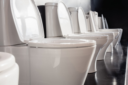 empty the bowel: Row of white ceramic toilet bowls on black wall.