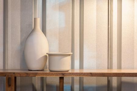 White ceramic vase and flowerpot on a wooden shelf against corrugated wall. Stock Photo