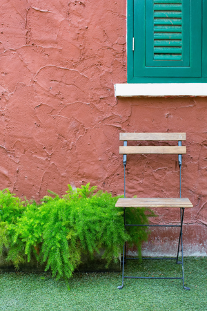 wooden chair with orange cement wall and green shutters window.