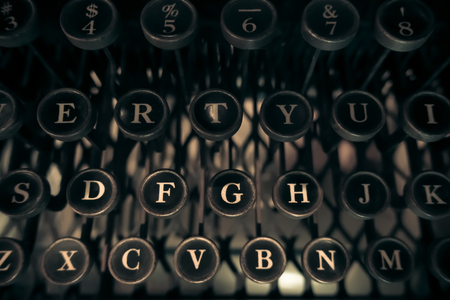 Capital alphabets on antique typewriter in dark and vintage tone.