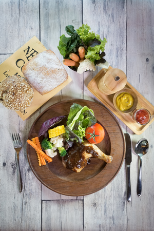 Chicken steak set with fresh vegetables and breads on a white wooden table with silverware and pepper grinder.