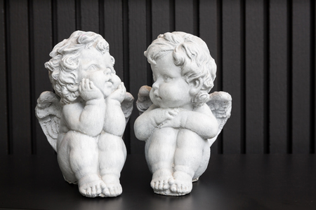 Little white angle sculptures decorated on top of table against black background.