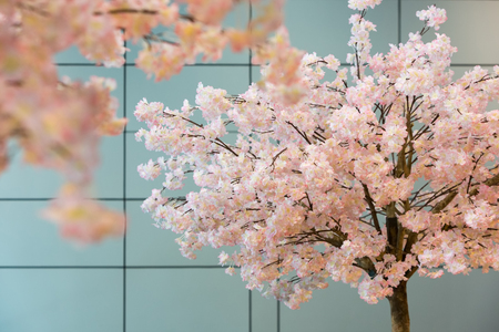 Artificial sakura blossom trees decorated in side a modern building. Stock Photo