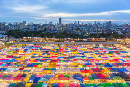 Bangkok, Thailand - 22 July 2016 : Train Night Market Ratchada with Multi-colored tents and business distric of downtown Bangkok in the background.