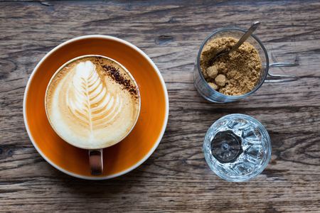 Cup of hot coffee in orange ceramic cup and plate with a small glass of syrup and brown sugar on a wooden table. Stock Photo