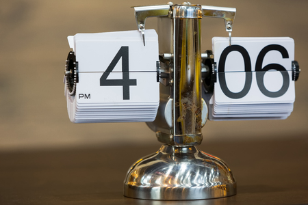 Old style silver flip clock on a wooden table Stock Photo