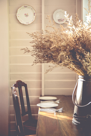Wooden dining table in vintage style with wooden chairs and dried flower in a tin jar on the table.