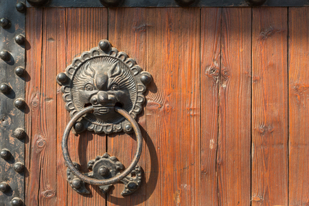 Brass door handle and knocker in chinese style on a old wooden gate. Stock Photo