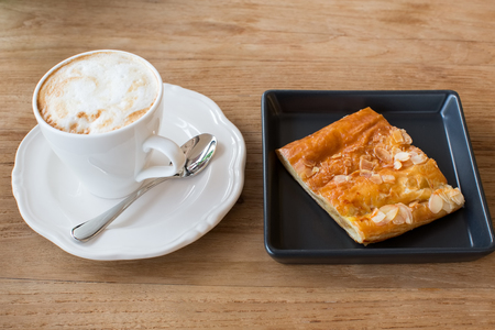 Cup of hot coffee in white ceramic cup and a piece of apple pie with almond in a black dish on a wooden top table.