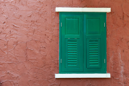 Colorful closed wooden window  on red wall in europe. Stock Photo