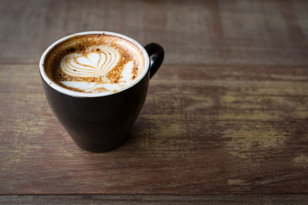 Hot cappuccino in black ceramic cup with beautiful latte art on wooden table.