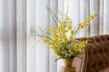 Wild yellow orchid in a ceramic vase decorated near a sofa and white curtain.