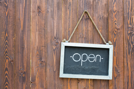Open sign on small blackboard hang on a wooden wall. Stock Photo