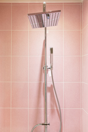 Close up of shower heads with colorful pink wall tiles. Stock Photo