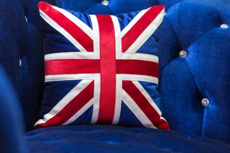 Vintage blue velvet sofa with England flag pillows.