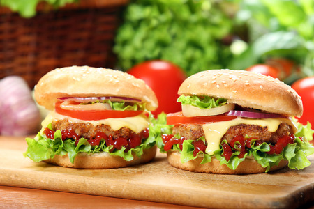 chicken burger: Homemade hamburger with fresh vegetables and cheese on wooden cutting board