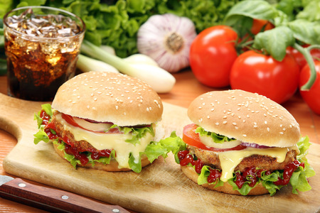 Homemade hamburger with fresh vegetables and cheese on wooden cutting board
