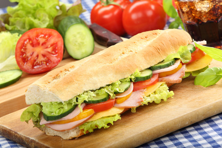Baguette salad submarine sandwich with ham cheese and tomato on wooden chopping board