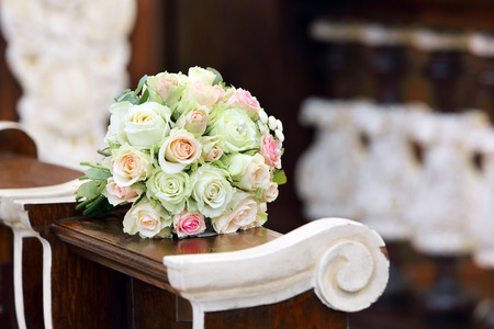 Bridal wedding roses bouquet on the hassock in the church during the marriage ceremony photo
