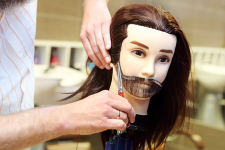 Barber student trimming brown hair using puppet and scissors photo