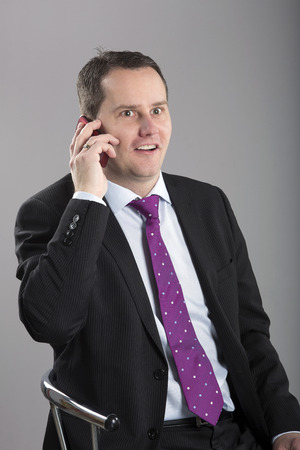 Portrait of middle aged businessman talking on mobilephone with surprised face photo