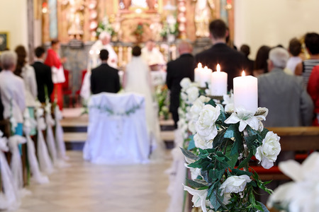 altar: Young couple during the wedding ceremony before the altar in a church full of people - selective focus on flowers