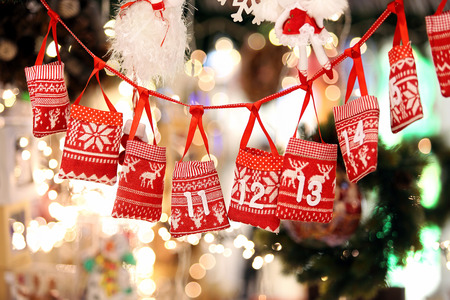 Small bags as Advent calendar with Sweets surprises hanging on a ribbon against lights blurred background Foto de archivo