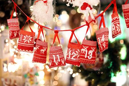 Kleine Taschen als Adventskalender mit Süßigkeiten Überraschungen an einem Band gegen Lichter verschwommen Hintergrund hängenden
