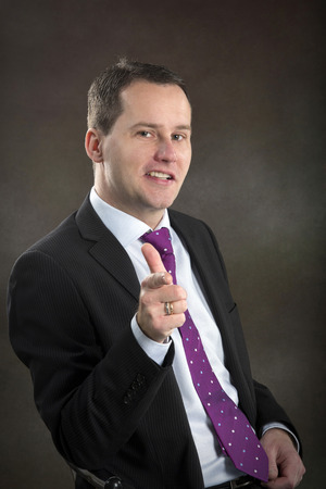 Portrait of middle aged businessman pointing his finger at the camera
