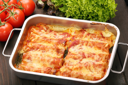 Cannelloni baked in a roasting pan on a wooden background Standard-Bild
