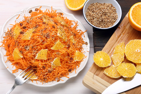 roasted sesame: Salad from carrots with orange, raisins and roasted sesame seeds on a wooden background