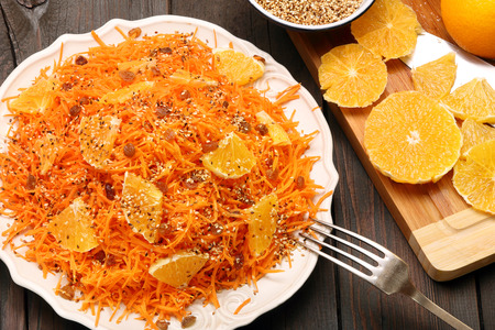 roasted sesame: Christmas salad from carrots with orange, raisins and roasted sesame seeds on a wooden background