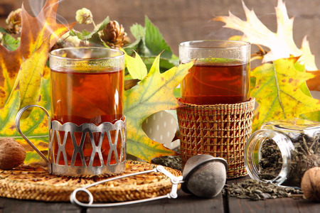 Hot green tea in a glass on a wooden background with autumn leaves photo
