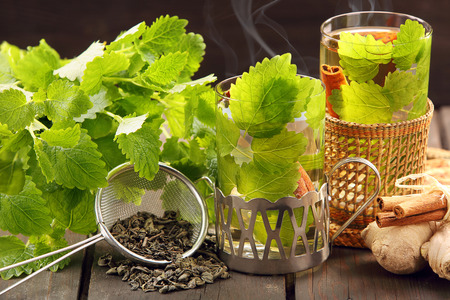 Hot green tea in a glass on a wooden background with lemon balm leaves and cinnamon photo