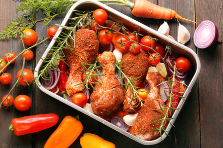 Chicken drumsticks prepared for roasting in a pan with vegetables on a wooden background Stockfoto