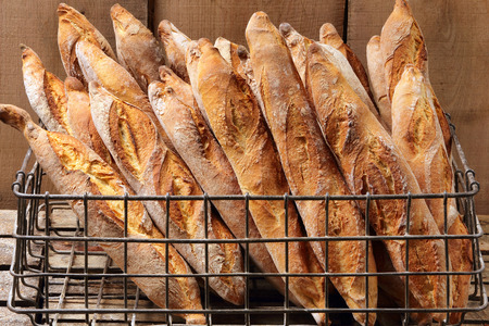 french bakery: French baguettes in metal basket in bakery