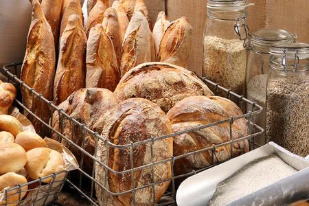 金属バスケット木製の背景にベーカリーで焼きたてのパン 写真素材