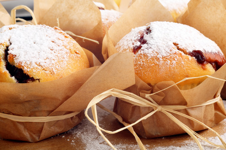 sprinkled: Muffins with jam sprinkled with powdered sugar on wooden tray