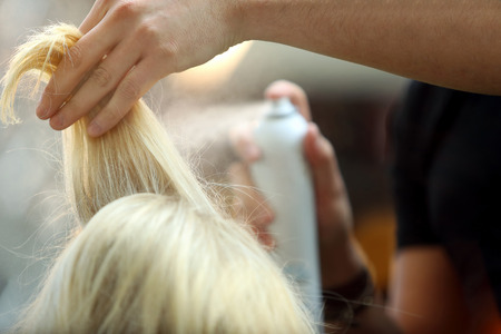 Hairdresser sprayed blond hair Standard-Bild