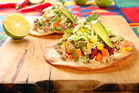 food dish: Tostadas with ground beef and vegetables on wooden background