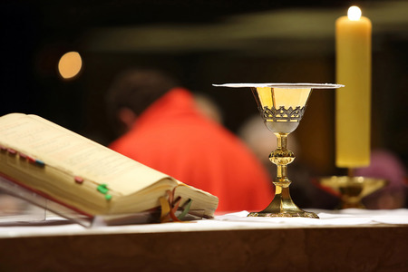 Golden chalice on the altar during the distribution of Holy Communion