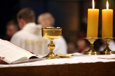 Golden chalice on the altar during the distribution of Holy Communion photo