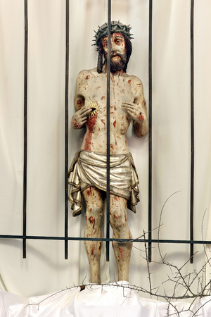 crucify: Jesus behind bars in prison. Wooden figure of Jesus in the church during Easter.