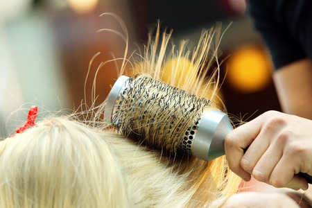combing hair: Hairdresser combing hair of young girl by hairbrush and hair dryer