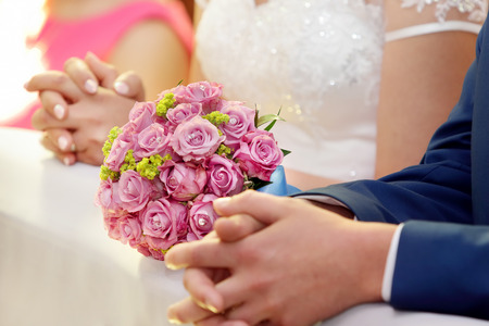 Newlyweds with wedding rose bouquet at the church photo