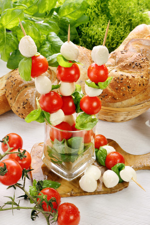 Caprese salad, skewers with tomato and mozzarella with basil