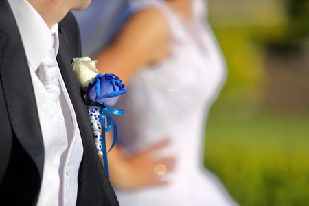 buttonhole: Groom with wedding blue rose buttonhole outdoors