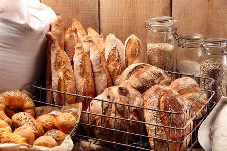 Fresh bread in metal basket in bakery on wooden background