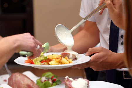 serves: Chef serves portions of food at a party Stock Photo