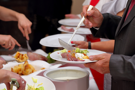 buffet dinner: Chef serves portions of food at a party Stock Photo
